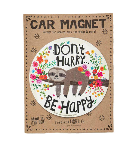 "A white circular car magnet with a picture of a lazy sloth lying on a tree branch with flowers all around. There is black text on the top and bottom that reads ""Don't Hurry, Be Happy"""