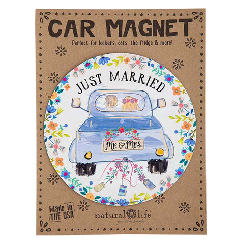 "This circular magnet has a design of a man and woman driving in a truck together. The truck's rear license plate says, ""Mr. and Mrs."" in black lettering. Above the truck are the words, ""Just Married"" in black lettering. Blue and orange flowers surround the truck. The magnet is shown attached to its cardboard packaging."