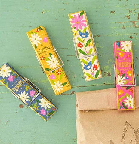 Set of 4 multi-colored floral pattern chip clips, 3 are lying on the table while the fourth is clipped to a paper bag.