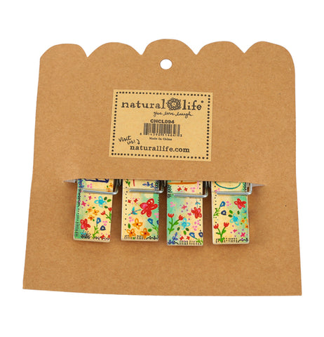 Backside view of set of 4 bag clips with colorful flower designs inside their brown paper packaging with Natural Life sticker placed in the center.