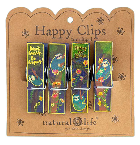 "These four bag clips all feature a design of sloths resting in and climbing up trees in different positions. The first clip on the left says, ""Don't Hurry Be Happy"" in yellow lettering. The third clip to the right says, ""Hang in There"" in black lettering. All the clips are attached to their cardboard packaging with the words, ""Happy Clips for Chips"" at the top in black lettering. The logo, ""Natural Life"" sits at the bottom."