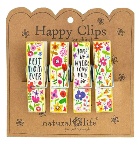 "These four bag clips all feature a design of red, pink, and purple flowers. The first clip on the left says, ""Best Mom Ever"" in black lettering. The third clip to the right says, ""Home is Where Your Mom Is"" in black lettering. All the clips are attached to their cardboard packaging with the words, ""Happy Clips for Chips"" at the top in black lettering. The logo, ""Natural Life"" sits at the bottom."