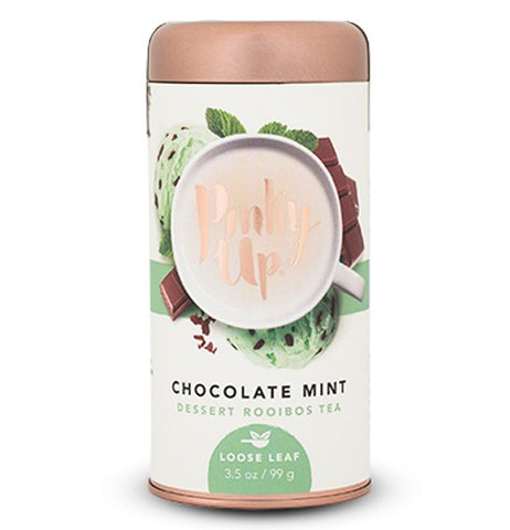 This copper container of Pinky Up Chocolate Mint Dessert Rooibos Tea shows background of chocolates and spearmint leaves.