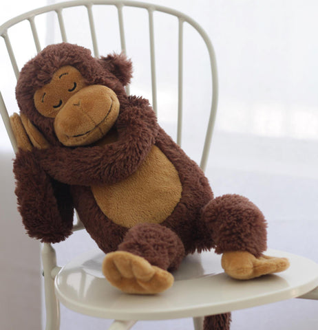 The monkey toy is shown in a sleeping pose on a chair.