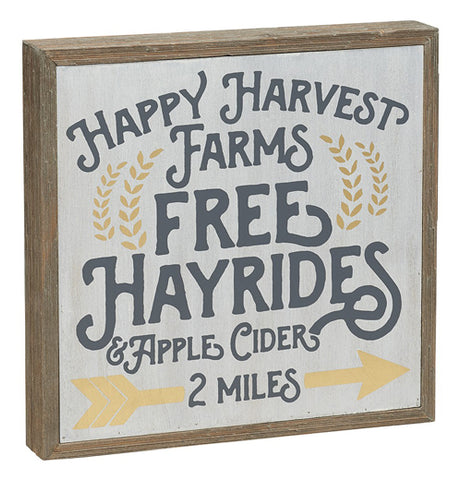 "a square box sign that says ""Happy Harvest Farms"", ""Free Hayrides"", ""& Apple Cider"", and ""2 Miles"" on it with decoration of gold leaves and an arrow"