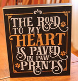"The black wooden box sign with the words, ""The Road to my Heart is Paved in Paw Prints"" in white and gold lettering is shown sitting on a wooden table."
