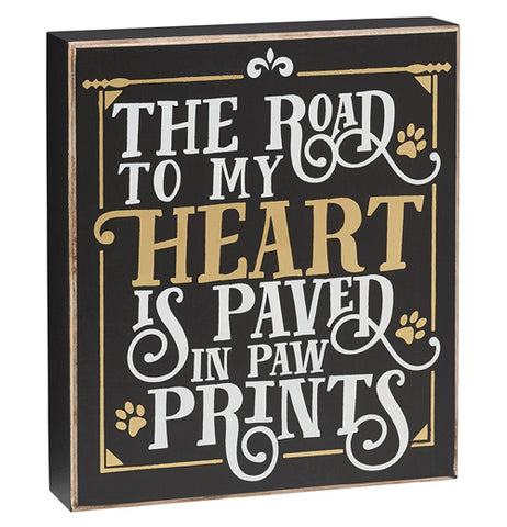 "This black wooden box sign features a golden outline around its edges. In addition to a few golden dog footprints, it has the words, ""The Road to my Heart is Paved in Paw Prints"" in mostly white lettering. The word, ""Heart"" is in golden lettering."