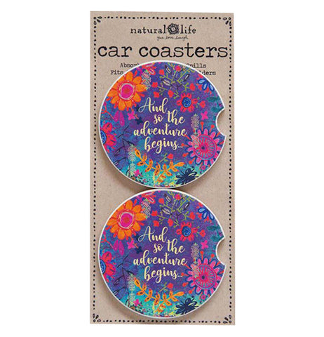 "The (Set of 2) ""Adventure Begins"" Car Coaster packaged has colorful floral design with gold foil words that says, ""And So the Adventure Begins""."