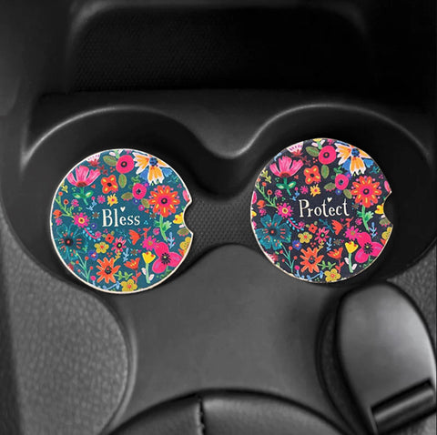 Two round coasters with floral patterns sit in a car's cupholder.
