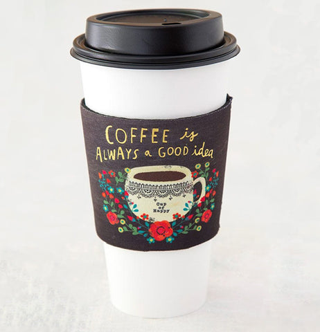 "A reusable white coffee cup that has a cozy sleeve that reads ""Cup of Happy""."