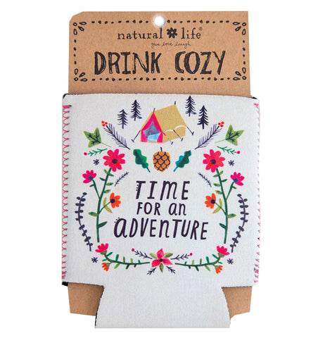 "This white drink cover is shown in its brown cardboard packaging. The cozy has a design of a pink and brown tent surrounded by pink flowers, pine trees, and pineapples. In the middle of the cover, in black lettering, are the words, ""Time For An Adventure""."