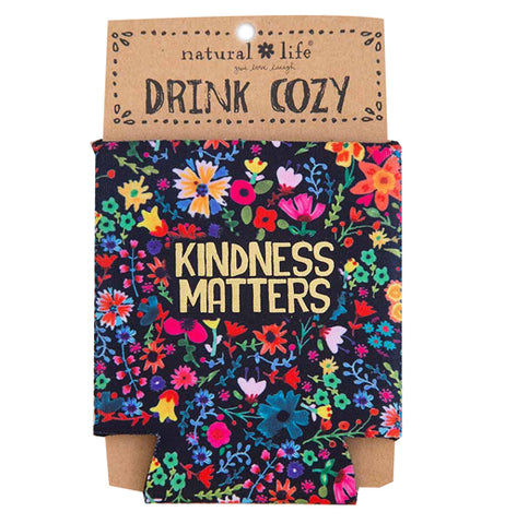 "This black drink cover is shown in its brown cardboard packaging. The cover has a design of pink, purple, red, and yellow flowers. In the middle of the cover, in yellow lettering, are the words, ""Kindness Matters""."