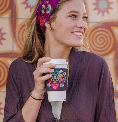 A woman is shown holding a coffee cup with the flower and heart design drink cozy wrapped around it.