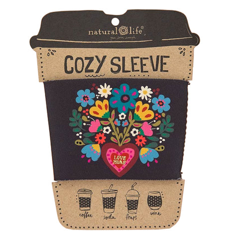 This black drink cozy attached to its cardboard packaging features a circular design of blue, yellow, and pink flowers with a pink heart in its center.
