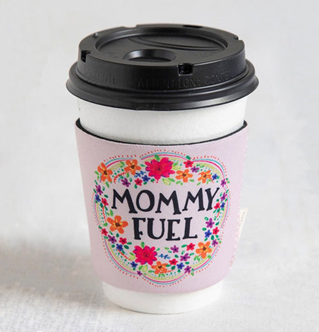 The Mommy Fuel Cozy is on a reusable white coffee cup and black lid.