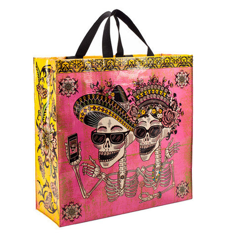 "This Shopper ""Day of the Dead""reusable shopping bag has four flowers one in each corner of the bag with two skeletons as a couple taking a selfie together warring Mexican traditional head wear and cool shades.There is also a pretty pink background."