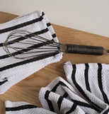 An egg beater is shown lying on top of the white towel with black stripes on a wooden table.