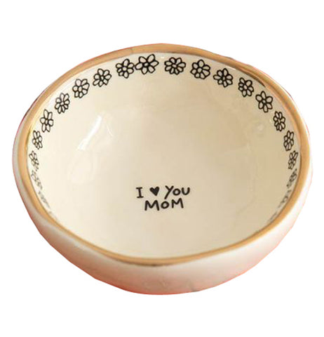 "The Trinket Bowl has a black text in the center of the yellow bowl that says, ""I Love You, Mom"" with floral designs on the inside and gold foil lined on the rim."