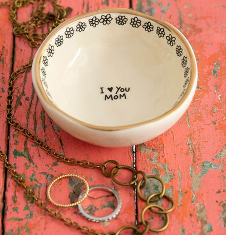 "The ""I Love You, Mom"" Giving Trinket Bowl sits on a salmon colored wooden table with some jewelry laying near it."