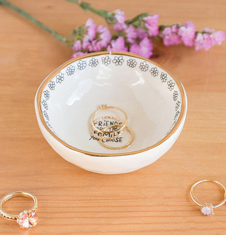 "The ""Friends are Family"" Giving Trinket Bowl sits on the table with two rings inside along flowers and two more rings outside the bowl."