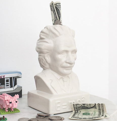 This bank is a white statue of the head of Albert Einstein. with money sticking out of it