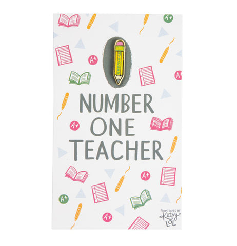 Yellow enamel pencil pin with #1 Teacher written on it.  It's attached to a post card decorated with school related pictures.