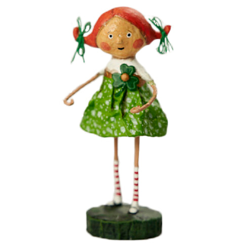 A resin figurine of a red haired girl standing on a black base. The girls hair is tied up in two ponytails with green ribbons. She wears a white and green dress with a four leaf clover pinned to her chest, red and white striped socks, and Mary Jane shoes.