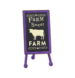 "Mini sign that says ""farm sweet farm"" on it. There's a cow between the words sweet and farm. It has a black background and a purple rim."