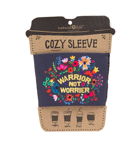 "This black drink cozy attached to its cardboard packaging has a design of pink, red, blue, green, and yellow flowers covering it. In the middle of the flower design are the words, ""Warrior Not Worrier"" in yellow lettering."