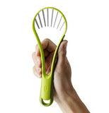 Green avocado slicer & peeler in hand.