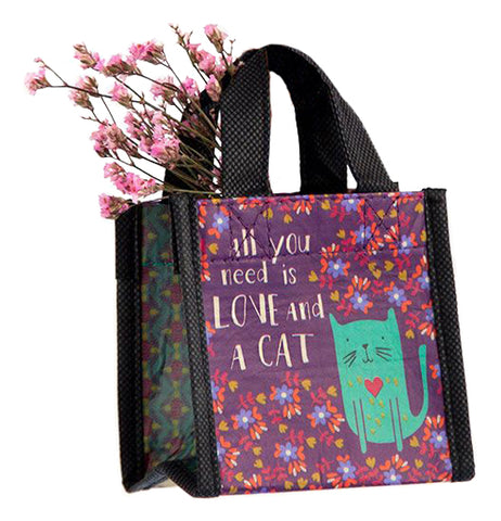 "The Recycled ""All You Need Is Love and a Cat"" Tiny Bag features a floral design with a green cat and words on a purple background."