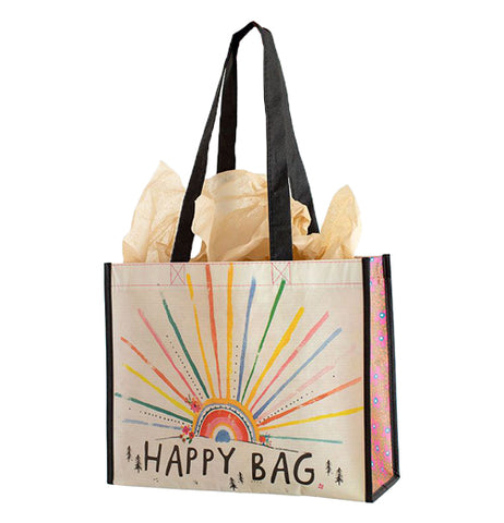 "This cream colored bag with pink sides and black handles has a multi-colored sun rising over a horizon with the words, ""Happy Bag"" below in black lettering."