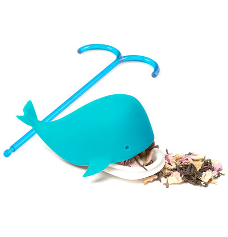blue whale tea infuser-with its mouth open with tea leaves coming out and its dipping stick laying beside it.