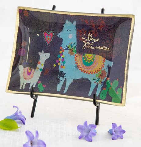 The dark purple glass tray with the white and blue llamas is shown sitting on a black metal stand surrounded by purple flowers.