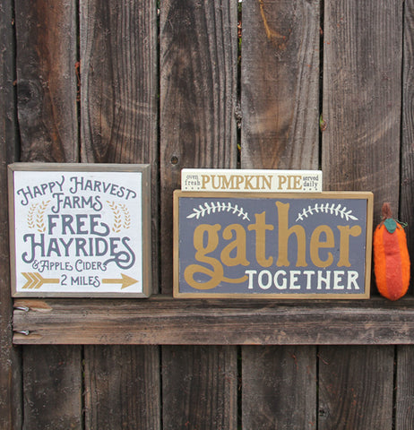 "a box sign that primarily says ""Free Hayrides"" siting against a wood background with two more box signs, one says ""Pumpkin Pie"" and the other says ""Gather Together"" and a small orange pumpkin on the right"