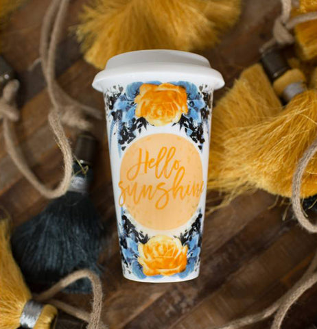 "The ""Hello Sunshine"" Ceramic Travel Mug lays on a bunch of yellow and black tassels."