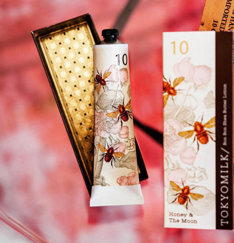 Tube of shea butter lotion on its gold colored inner box next to its bee and floral design outer box on a pink background.