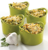 Four green ramekin dishes are shown with quiches in them and a garlic standing next to one of them.