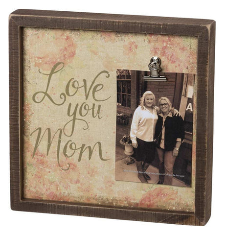 "The Inset ""Love You Mom"" Box Frame has faded floral designs with the photo on the right, and words that says, ""Love You Mom""."