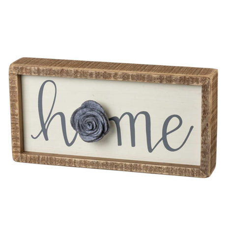 "The Inset ""Home"" Box Sign has a box that says, ""Home"" with a gray felt flower over a white background."