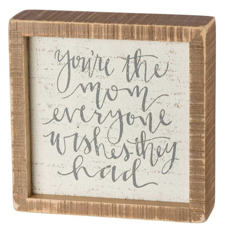 "The Inset ""The Mom"" Box Sign has text that reads, ""You're the Mom Everyone Wishes They Had"" in gray words with the brown wooden frame on the outside."