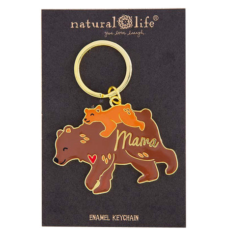"This key chain with a golden ring is shown tethered to its black cardboard packaging, which has the words, ""Enamel Keychain"" at the bottom in yellow lettering. The metal sculpture is a brown bear mother carrying a cub on her back. The word, ""Mama"" are spelled across the mother bear's back leg in golden lettering."
