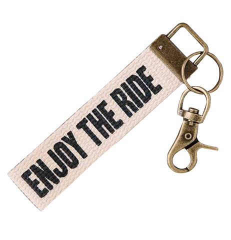 "This key fob has a small white banner with the words, ""Enjoy the Ride"" written in black lettering across it."