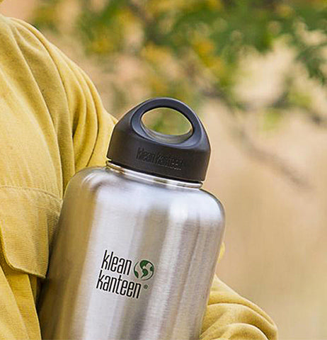 "The steel black lid is shown sealing the top of a ""Klean Kanteen"" steel water bottle."