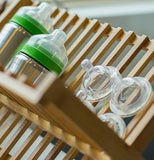 The clear silicone nipples are shown lying on a wooden dish rack.