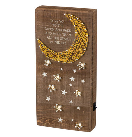 "Wooden board with a moon made of pins and string as well as the stars making up a version of the peaceful night sky. It even has a ""moon and back"" quote printed on it."