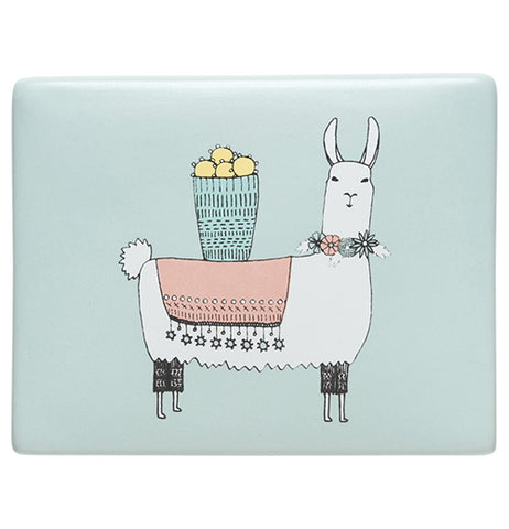 A top of a jewelry box. It's mostly pastel blue. In the middle there is a cartoonish white llama. The llama has pastel pink blanket and blue basket of pastel yellow fruit on its back and a floral wreath around its neck.