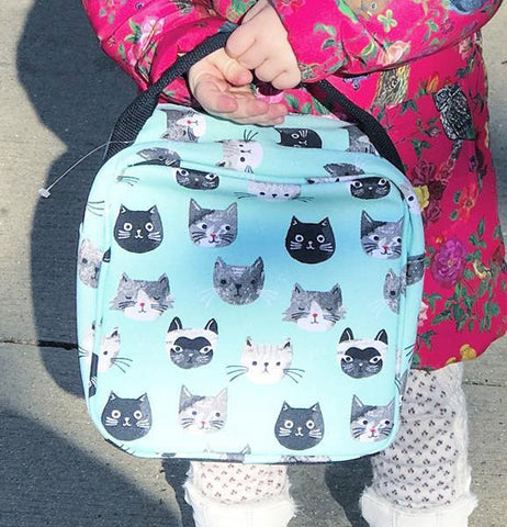 a person holding a feline -themed lunch bag.