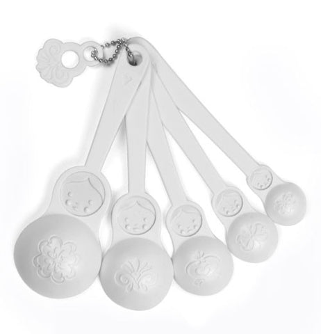 These white measuring spoons are shaped like Matryoshka dolls, ranging from greatest to smallest going from left to right.