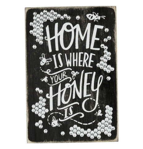 A black and white wood magnet. Bees and honeycombs surround the text.